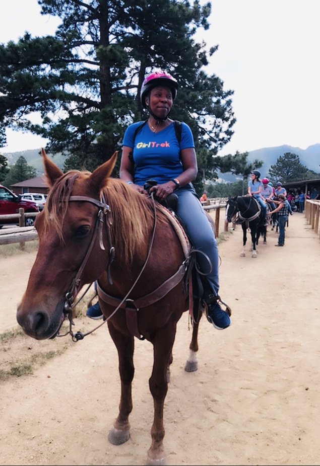 Lisa mounted on a horse in the Rocky Mountains