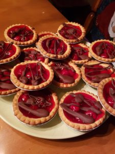 14 mini cherry chocolate tartlets on a plate