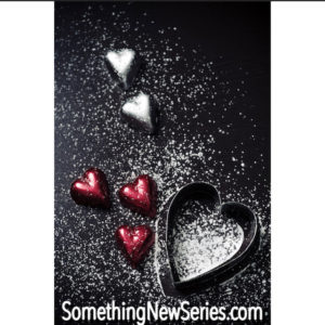 red and silver foil hearts on a black background sprinkled with confectioners sugar, the words something new series dot com are at the bottom of the image